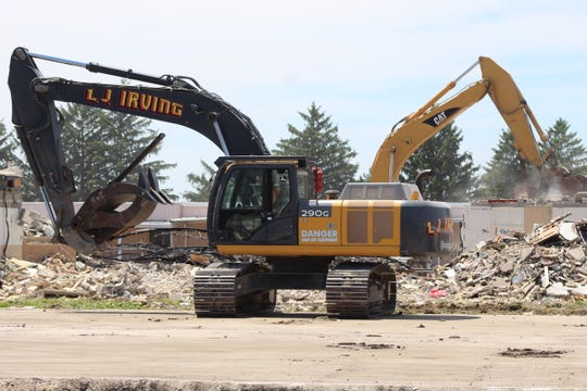 Work crews from L. J. Irving Demolition tear down sections of the old Otis Elementary School Wednesday. The new Otis Elementary School building is being constructed adjacent to the old building and is scheduled to open this fall.