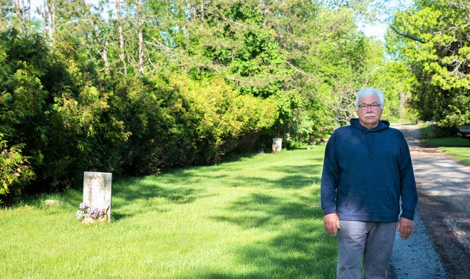 The Potter's Field area of Evergreen Cemetery in Oconto is seen over the right shoulder of Peter Gabrielson of Oconto. He is working a construction of a memorial on the site.