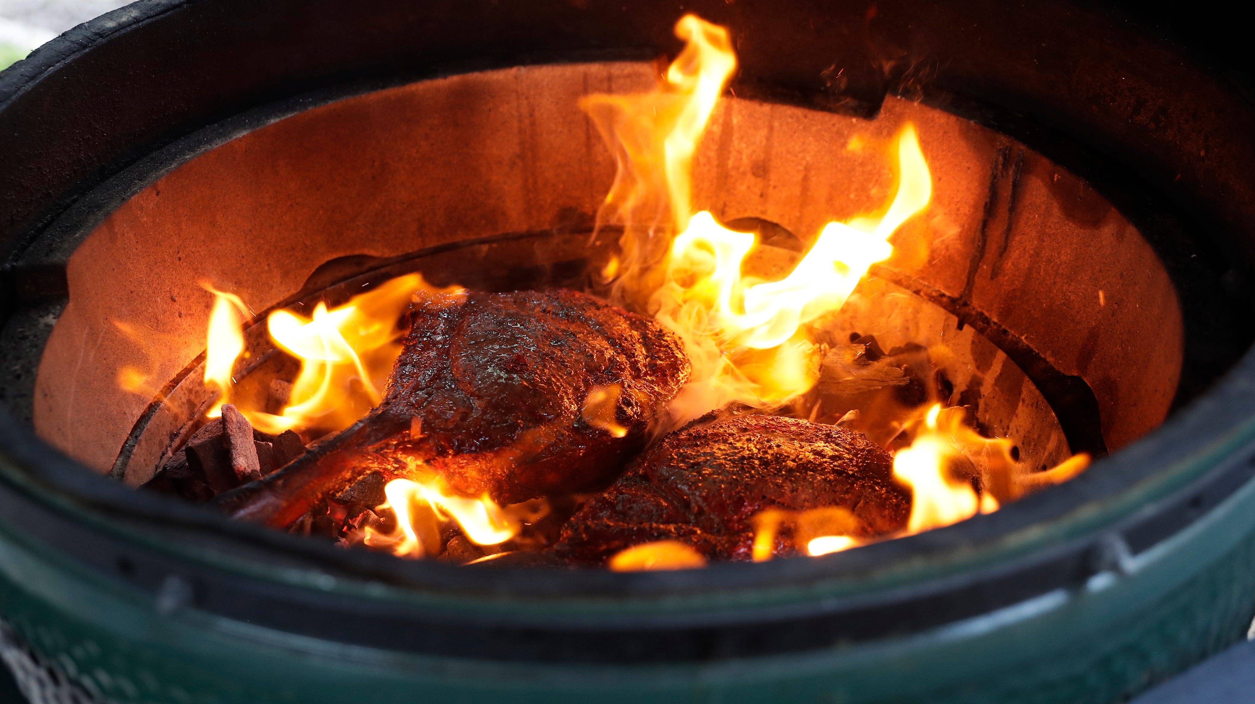 Tossing steaks on a hot bed of coals is one of Schemm's favorite grilling methods.