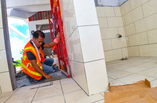 Manny Acordon, a mason worker with ProPacific Builders, finishes laying tiles within the restroom facilities at the Chinese Park in Tamuning on Thursday, June 18, 2020.