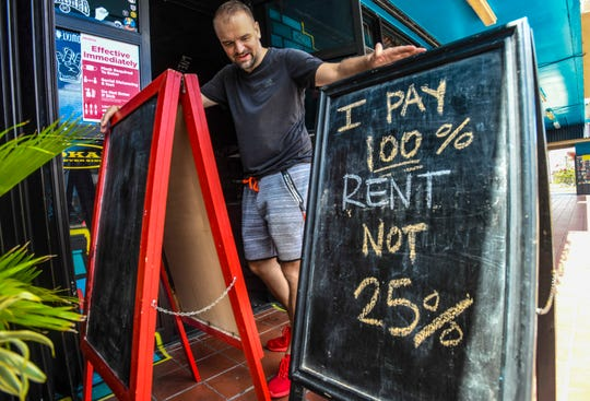 Owner Thomas Peinhopf checks over one of two signs that expresses his sentiment regarding patron limits, posted just outside his Livehouse Guam bar in Tumon, on Thursday, June 18, 2020. Peinhopf says the bar temporarily closed its doors on March 20, due to mandates imposed in relations to the COVID-19 pandemic. On Friday, the closures will be lifted and bars will be allowed to serve customers again but with certain restrictions, that includes total occupancy not exceeding 25%.