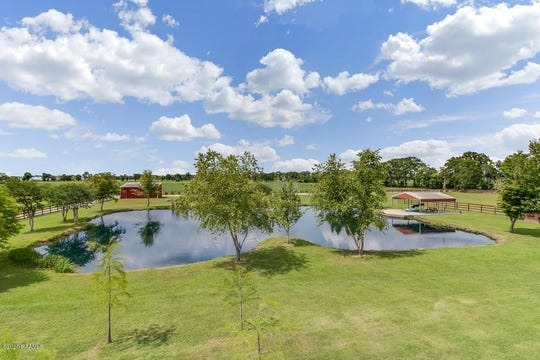 A huge, fully stocked pond with fishing pavilion and boat launch is beside a large barn with horse stables and a large exterior storage barn.