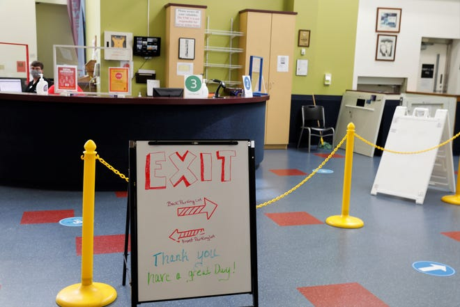 A sign directs patrons of the Robert K. Fox Family YMCA through the lobby as staff members wait to take temperatures at the door. As the facility prepares to reopen, changes like this have been implemented throughout the facility.