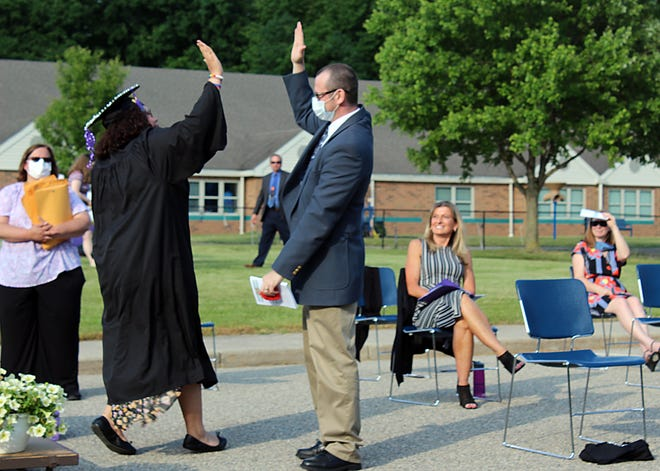 Alysia Gordon (left) and Principal Markus Muennix exchange an air high-five after she receives her diploma during Kensington Woods Schools graduation on Friday, June 12, 2020.