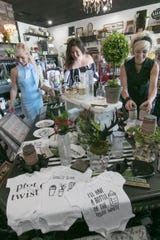 That's What She Shed co-owners, from left, Madelyn Vyletel, Kristy Ellis and Tammy Metz set out products on a table inside their newly opened Hartland Township store Thursday, June 18, 2020.