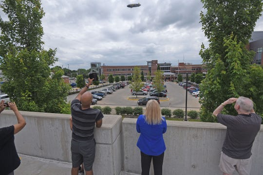 """People from inside and outside of the hospital gathered to watch the Goodyear blimp Wingfoot Three circle Ohio Health-Mansfield Hospital several times Thursday morning. The blimp has been flying all over Northeast Ohio since Monday as part of a """"Sky High Thank You"""" tour to show appreciation for hospital and essential workers who continue to serve on the front lines during the novel coronavirus pandemic."""