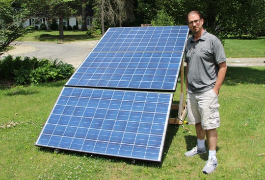 Clean energy entrepreneur Jason Jordan displays the solar panel array in the front yard of his home in Marion. It's a residential power unit that he is testing for potential mass production and distribution. Jordan is the founder and owner of Jordan Energy Alternative.
