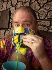 "GTSouth Geek & Gaming Tavern owner Mike Taylor drinks through a flap in his ""Minions"" mask."