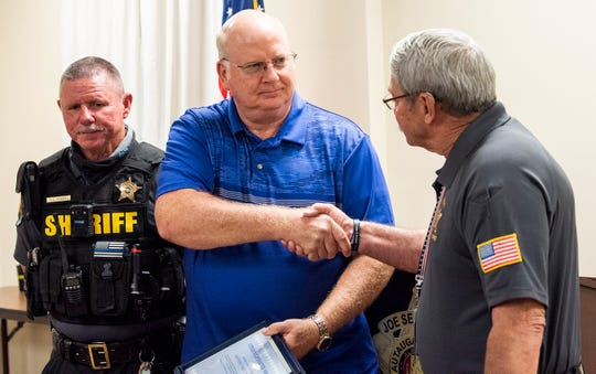 Autauga County Sheriff Lt. S.D. Adams, left, looks on as Autauga County Sheriff Joe Sedinger, right, presents Jeffrey Williams with a citizen lifesaver award at the sheriff's office in Prattville, Ala., on Thursday June 18, 2020. Williams was awarded for stopping his car and waking a man up and getting him out of his home that was on fire on Memorial Day morning.