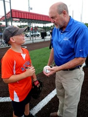 Smyrna Town Councilman H.G. Cole, right asks Bryce Victory, 9, left to sign the ball Cole threw during the ribbon-cutting ceremony for Cedar Stone Community Park on Wednesday, June 17, 2020, in Smyrna. Victory served as the catcher for Cole's first pitch at the park, where one of the four baseball fields is named for him.
