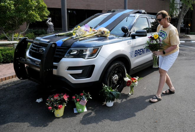 KaKa Ray of Brentwood places flowers at the memorial outside the police department for Officer Destin Legieza who was killed in a two-vehicle crash on Franklin Road Thursday, June 18, 2020, in Brentwood, Tenn.