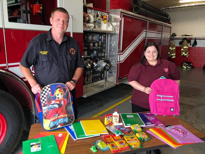 Newark Township Lieutenant Casey Tucker (left) and Salvation Army Lieutenant Kaitlyn Haddix (right), display backpacks and school supplies being sought for donation in the Licking County Back 2 School Bonanza Donation Blitz.