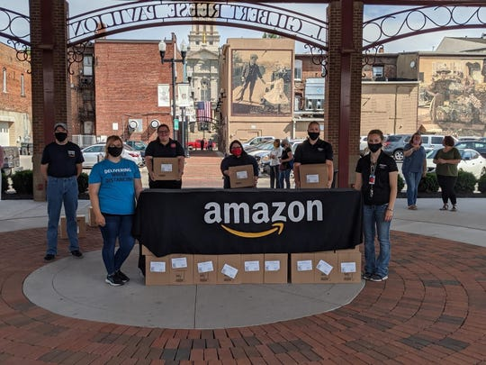 Amazon associates and representatives from Licking County nonprofits pose with boxes of hand sanitizer as part of a $90,000 donation.
