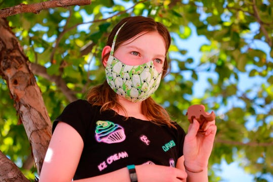 Rose Uberuaga, 12, poses with a 3D- printed plastic elephant she designed remotely during a summer camp after her instructor printed it out and gave it to her in a parking lot on Wednesday, June 17, 2020, in Santa Fe, New Mexico.