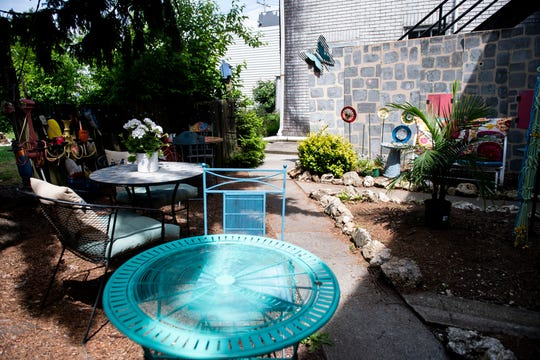 The rear of the shop features an outdoor area with seating and lawn ornaments for sale.