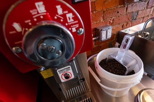 Dark-roasted coffee beans sit in a bucket on a counter inside Red Kettle Coffee Roasters.