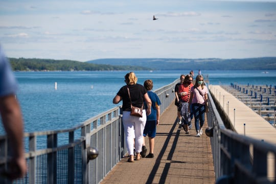 Several people, some with masks and some without, stroll along the pier that juts out Skaneateles Lake on Monday, June 15, 2020. Skaneateles, like many communities across New York, is slowly reopening after coronavirus.