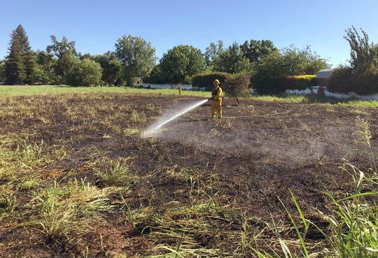 A firefighter puts out a quarter-acre grass fire off North Street in Anderson that started just after 4 p.m. Wednesday, June 17, 2020. It was one of several fires that broke out in the North State.