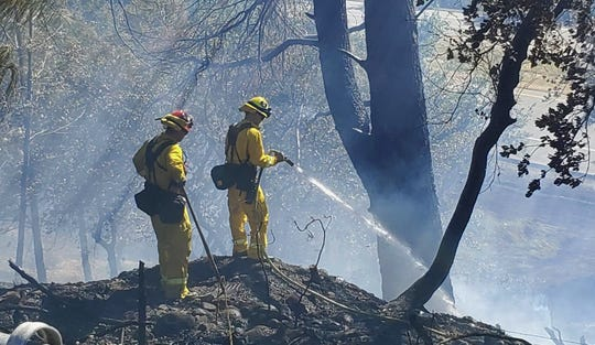 Fire crews extinguish a vegetation fire off Caterpillar Road in north Redding on Wednesday afternoon, June 17, 2020.