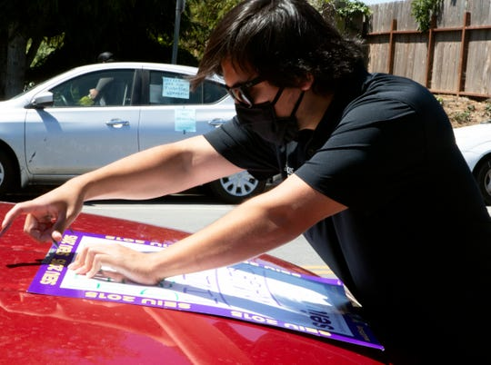 Cesar Sanchez, , an organizer with SEIU 2015, tapes a flier on a vehicle Thursday at the Windsor The Ridge Rehabilitation Center and Windsor Skyline Care Center in North Salinas. He and a few others showed up to call for more personal protective equipment for nursing home employees.