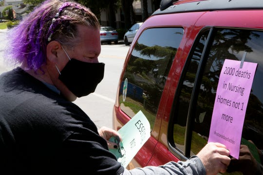 Nick Vitale, a certified nursing assistant at Windsor Monterey Care Center, tapes a flier on a vehicle Thursday at the Windsor The Ridge Rehabilitation Center and Windsor Skyline Care Center in North Salinas. He and a few others showed up to call for more personal protective equipment for nursing home employees.