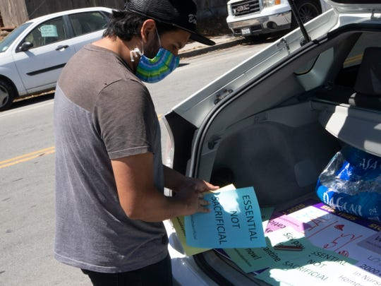 Vicente Vega, an organizer with SEIU 2015, prepares to tape fliers on a vehicle Thursday at the Windsor The Ridge Rehabilitation Center and Windsor Skyline Care Center in North Salinas. He and a few others showed up to call for more personal protective equipment for nursing home employees.