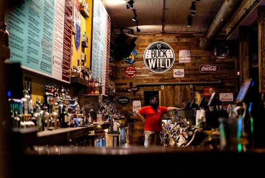 A bartender waits for customers at Buck Wild on West Sixth Street in downtown Austin as bars reopened on May 22.