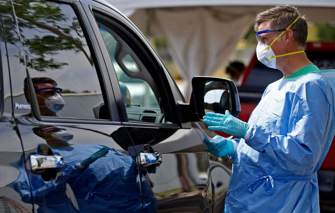 Zachary O'Neal, far right, works at the new location of the Shannon Medical Center drive through coronavirus testing site at 110 E. Twohig Ave. on Thursday, June 18, 2020.