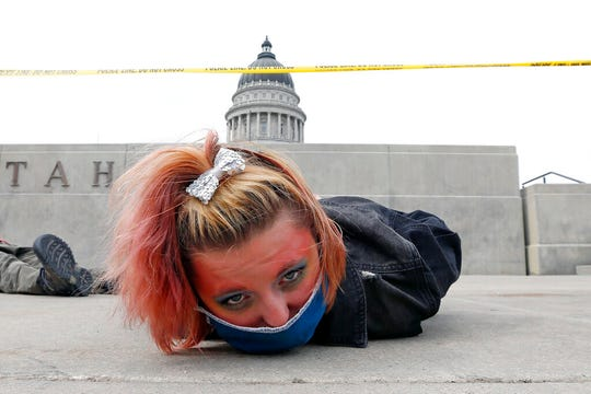FILE - In this June 6, 2020, file photo, a protester lies down for 8 minutes and 46 seconds during a protest at the Utah State Capitol in Salt Lake City. Utah lawmakers have taken a first step toward banning police officers from placing their knees on the necks of people being detained in the type of chokehold used by a Minnesota police officer in the death of George Floyd. (AP Photo/Rick Bowmer, File)
