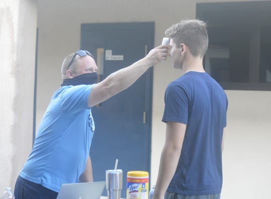 Central Valley Christian assistant football coach Nick Richardson checks a player's temperature on June 17, 2020 at CVC High School.