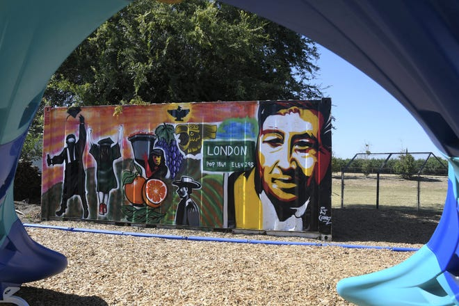 Artist AJ Gomez painted this mural on a storage container behind a new playground in London, California, as part of a beautification project at the London Community Center this spring. The mural features César Chávez, farm workers and graduates, as well as the London town sign. The side shows a father reading to his child and a girl reading a book.