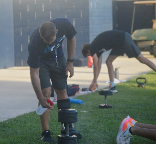 Central Valley Christian head football coach Mason Hughes sanitizes weights on June 17, 2020 at CVC High School. The Cavaliers are the first Tulare County football team to return to training amid the COVID-19 pandemic.