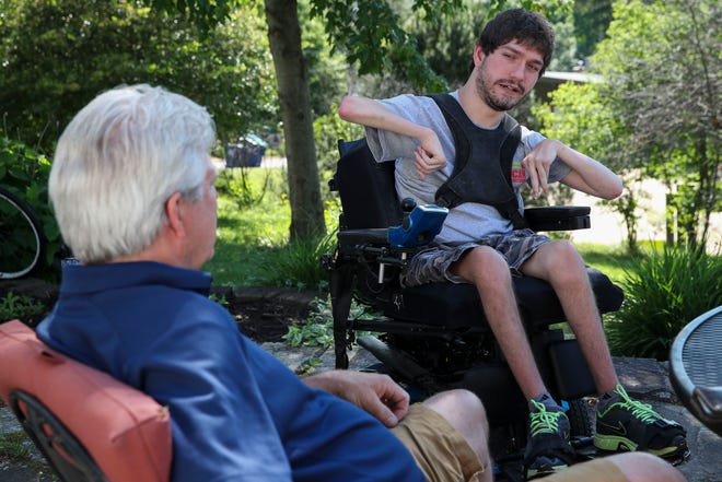 Michael Johnson talks during an interview with his father, Scott, on Wednesday, June 17, 2020, at their home in Wausau, Wis. Together, they own and operate both UCan Promotions and UCan Mobility, a business that distributes trackchairs for those with physical disabilities.
