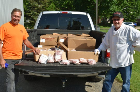 David Henning (left), Columbus operations manager for Vita Plus, and Jerry Stoddard of Stoddard's Meat Market & Catering, with UW pork products ready to be sent to food pantries from Stoddard's Market in Cottage Grove on 6/12/2020.