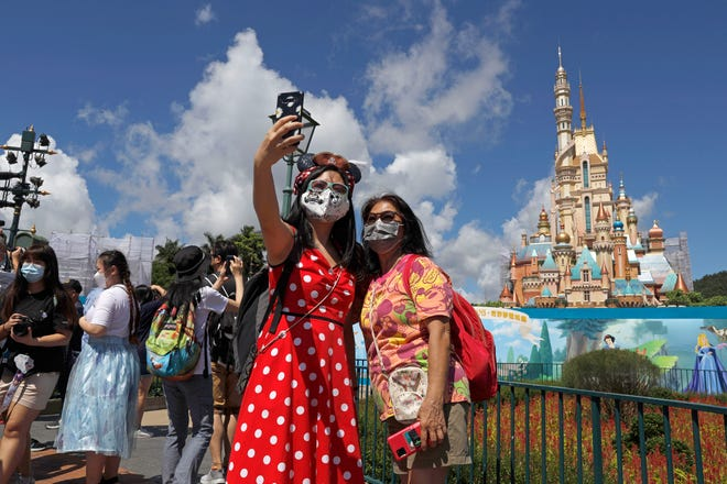 Visitors wearing face masks to prevent the spread of the new coronavirus, take a selfie at the Hong Kong Disneyland on Thursday, June 18, 2020.