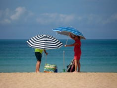 A couple adjust sunshades at the beach of Palma de Mallorca, Spain on June 16, 2020.