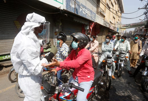 A police officer stops motorcyclists from entering a restricted area that is sealed off to control the spread of the coronavirus, in Lahore, Pakistan, June 18, 2020.