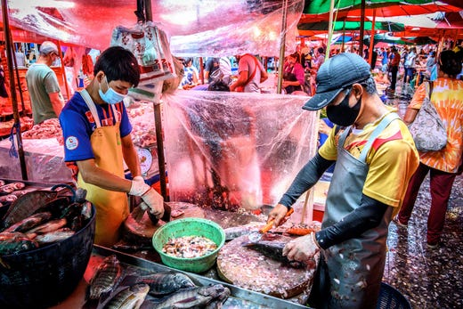 Vendors clean fish at Khlong Toei Market, the biggest fresh market in Bangkok, on June 18, 2020. A huge wholesale market has become the centre of focus for a new cluster of coronavirus cases in Beijing, where nervous local officials have begun mass testing, closing schools and neighbourhoods, and turned sharp scrutiny towards the food supply chain.