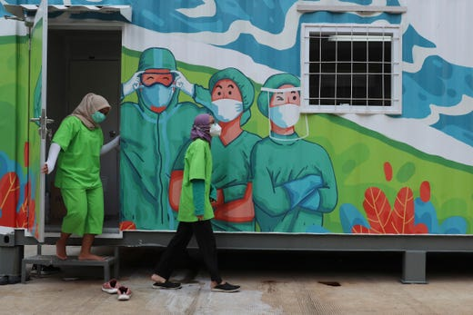 Health workers walk out of a mobile laboratory before analyzing samples collected during mass coronavirus tests in Jakarta, Indonesia, June 18, 2020.