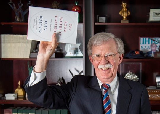Ambassador John Bolton mimics photos of President Donald Trump holding a Bible.