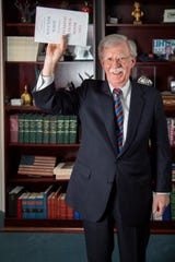 Former national security adviser John Bolton, at a USA TODAY interview about his White House memoir, mimics the controversial photograph of President Trump holding a Bible aloft in front of St. John's Church after protesters had been cleared from Lafayette Park.