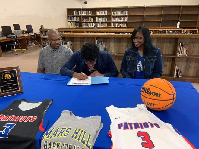 Elisha Barnette signs a commitment to continue his academic and basketball career at Mars Hill University.
