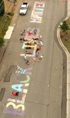 Living Life Leadership, the Kitsap Youth Activism Team and Karen Vargas (bottom) pose for an aerial photo after chalking Black Lives Matter down the middle of Park Ave. in front of the Marvin Williams Recreation Center in Bremerton on Friday, June 19, 2020.
