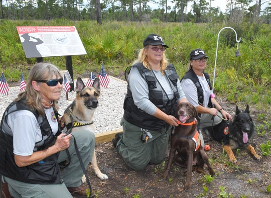 Several dogs from Florida Airboat Search & Rescue attended the event, including these three who were brought to the crash site in April of 2018, who found some of the remains. Left to right: Karen Gosnay with K-9 Niko, Whitney Hartz with K-9 Kamora, and Dina Wallace, with K-9 Akela.  Officials dedicated a memorial plaque to the seven crew members of a World War II bomber who died in a routine training crash in June of 1943 in what is now the Tosohatchee Wildlife Management Area, in Orange County, near Christmas.