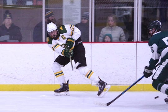 Burr and Burton's Joey McCoy fires the puck away from the boards during a game this season