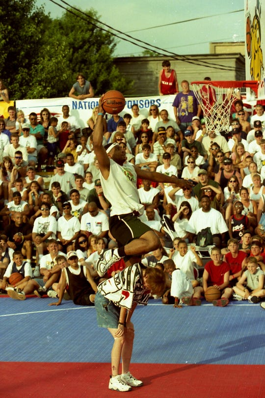 Randy Pennington leaps over a brave fan en route to the basket during the ever popular Gus Macker Slam-Dunk Contest in June 1997.