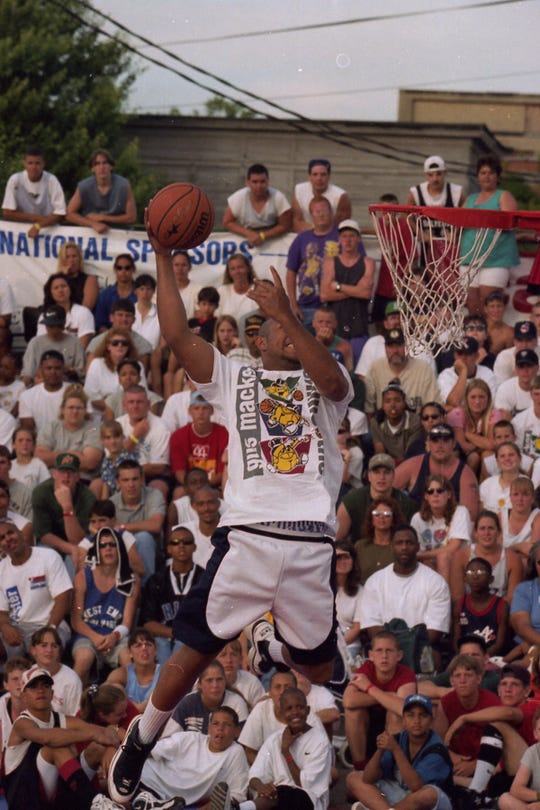 Former Chilicothe High School basketball player Richard Harris skies to the crown's delight during the Gus Macker Slam-Dunk Contest in June 1997.