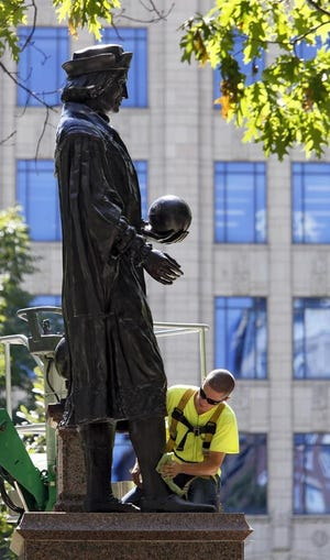 A worker gives the statue of Christopher Columbus on the statehouse grounds its biannual wax and buff back in 2013. Could the statue's days be numbered?