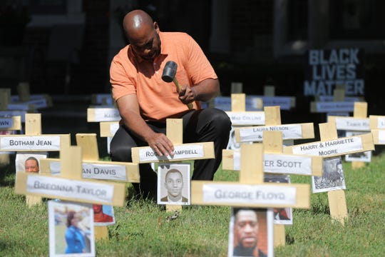 John Thorn secures one of the crosses he has put the front yard of his Detroit home on June 17, 2020.  Thorn has turned his front yard into a display in support of Black Lives Matter. The display includes pictures of not just people who have lost their lives to police brutality but it pays tribute to all African-Americans who have lost their lives to violence.