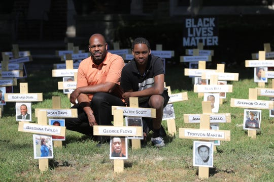 John Thorne and his son John Thorne II in the front yard of his Detroit home on June 17, 2020.  Thorne has turned his front yard into a display in support of Black Lives Matter. The display includes pictures of not just people who have lost their lives to police brutality but it pays tribute to all African-Americans who have lost their lives to violence.